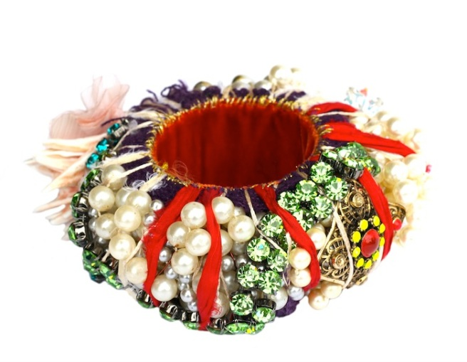 A colourful statement bangle made with a myriad of new and reclaimed components such as hand-painted vintage pendant, hand-made flower, white shell beads, coral to name a few.