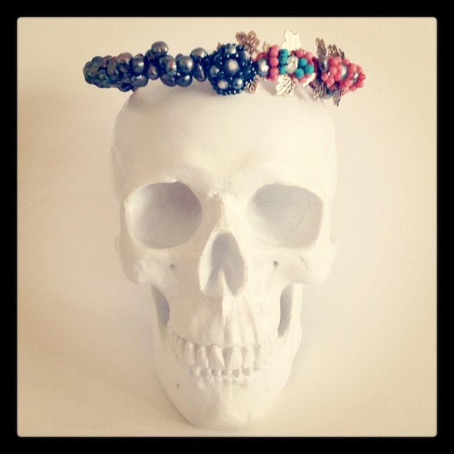 A skull with Jolita Jewellery headband, made  vintage headband with vine leaves, freshwater pearls, coral, turquoise and Swarovski crystals