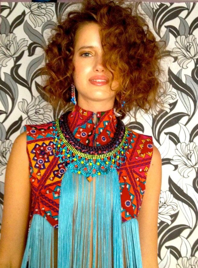 A model is posing for a tribal themed shoot in our hand-painted earrings and a colourful statement necklace made with double braid and crystals, hand-painted in peridot green, sky blue and neon