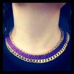 A necklace made with purple silk braid and gold tone chains