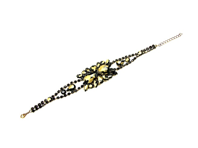 A bracelet, hand-painted in black and splashed with gold.