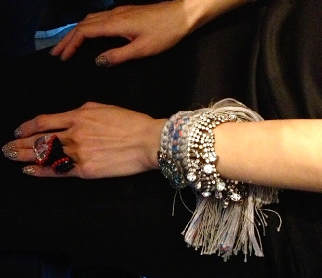 A model is wearing skull ring adorned with clear rock crystal and redo coral beads and braided bracelet with vintage brooch and crystals