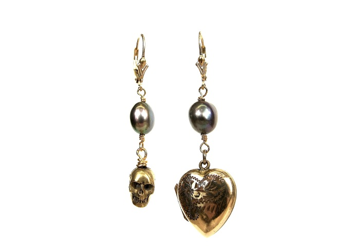 A pair of skull and heart earrings, made with bronze skull dipped in 24k gold, a hand-engraved heart and a black pearl on each earrings.
