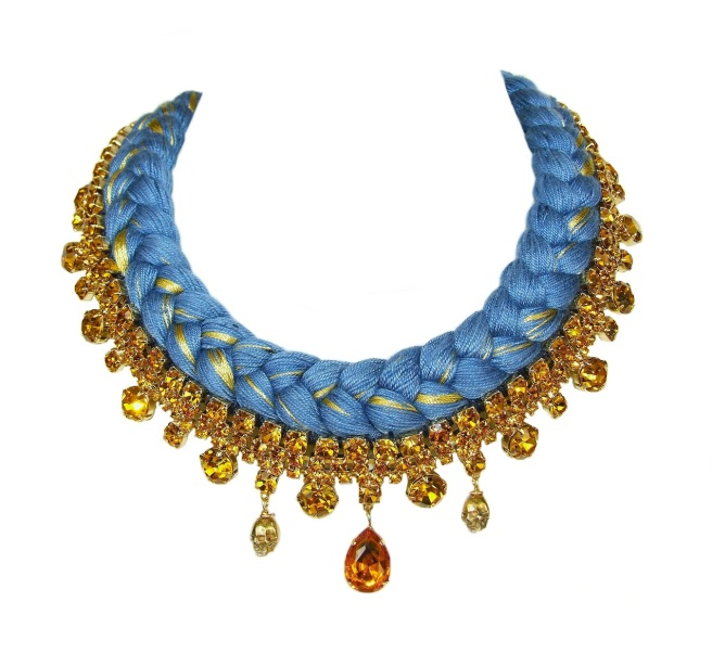 This statement necklace is made with blue braid, mixing in a hint of metallic and bohemian glass necklace, adorned with two skulls, dipped in gold.