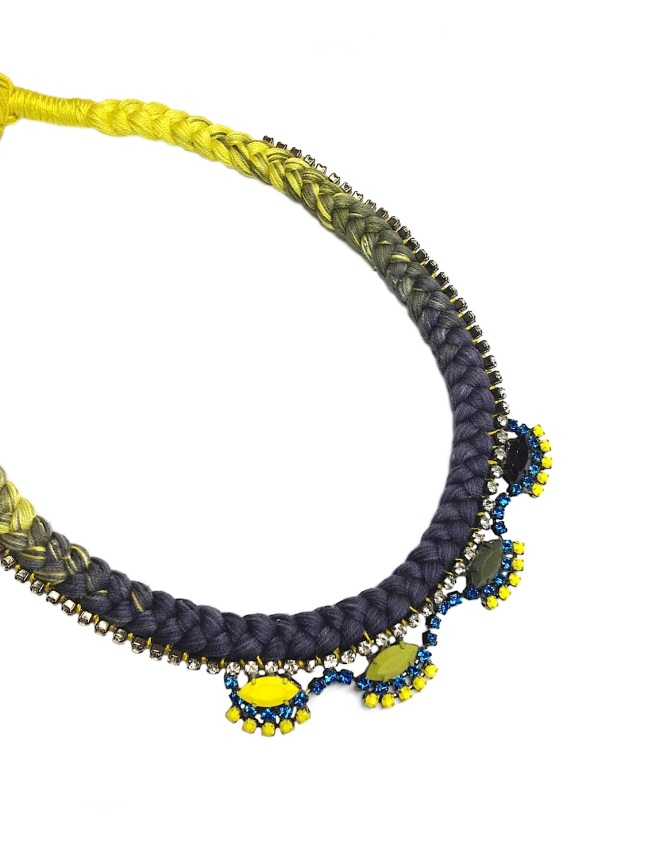 A colourful statement necklace made with dip-dyed braid in grey and yellow and rhinestones, hand-painted in yellow, lime green, khaki, black and blue