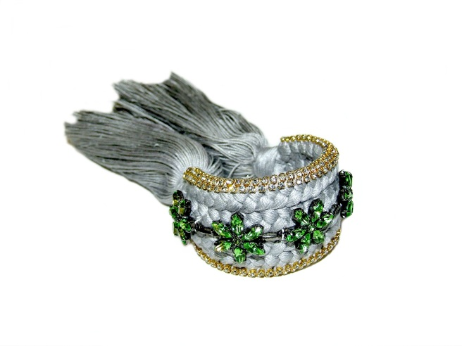 A custom-made braided silk cuff embellished with tiny clear crystals and green crystal flowers