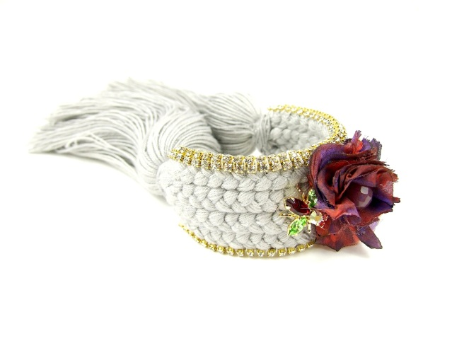 A custom-made braided silk cuff embellished with crystals, crystal bug, dipped in gold, and hand-made silk flower