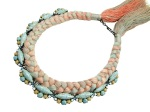 This limited edition statement necklace in soft pastels is made with faux turquoise caboshons and silk braid, mixing in soft shades of salmon pink and grey.