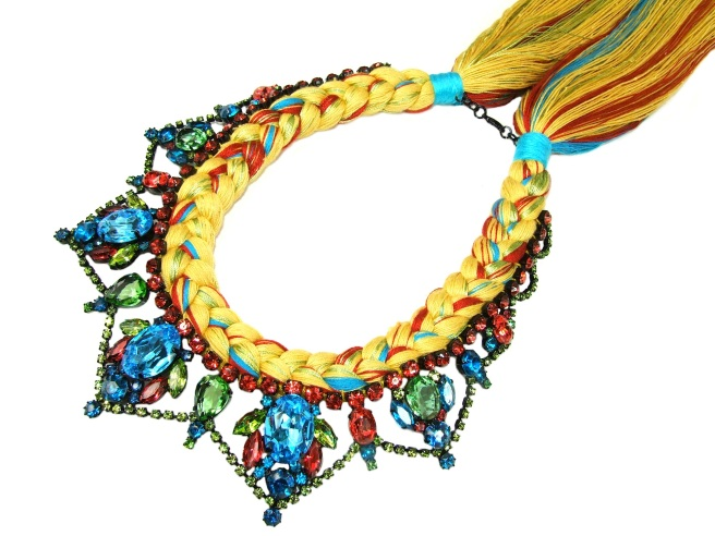 A colourful statement necklace made with crystals and silk braid in pastel colours of yellowish brown, purple, green, red and mixing in a touch of neon light blue.