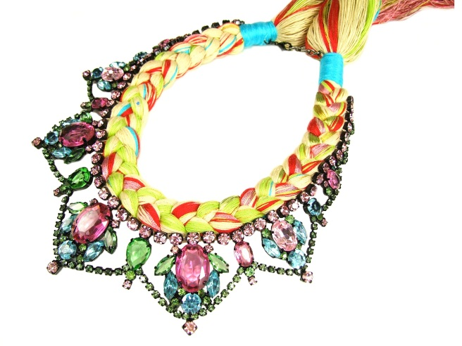 A colourful statement necklace made with crystals and silk braid in pastel colours of purple, green and blue.