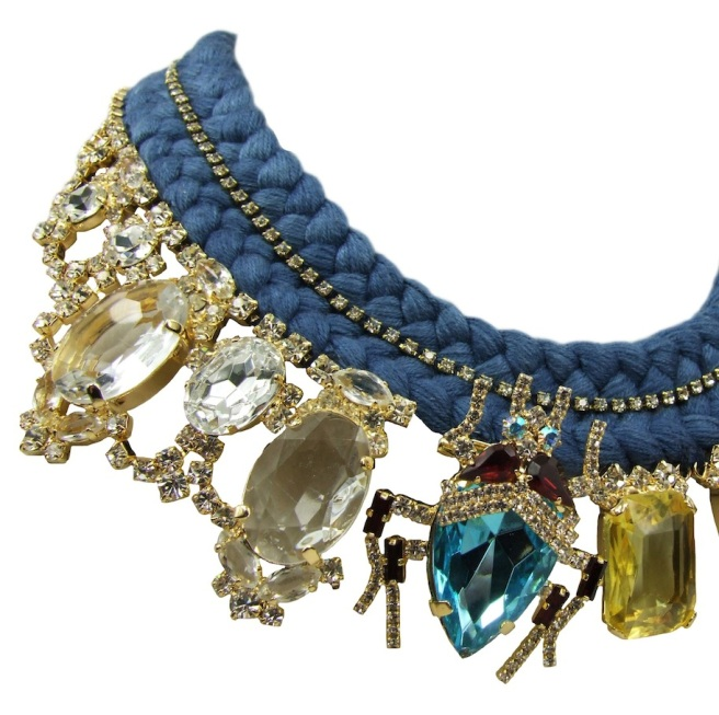 Luxury statement necklace made with double collar silk braid, embellished with crystals, and an array of deconstructed jewels, dipped in gold