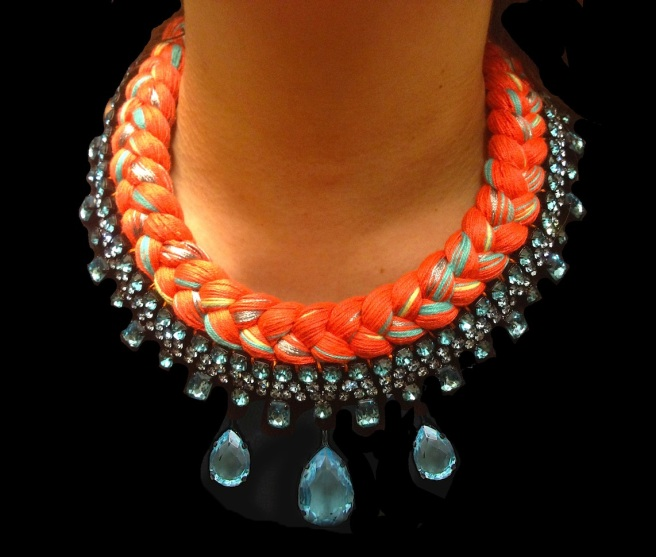 A colourful braided statement necklace in orange silk braid, mixing in turquoise, metallic grey and canary yellow silks, made with Bohemian glass rhinestones in light blue