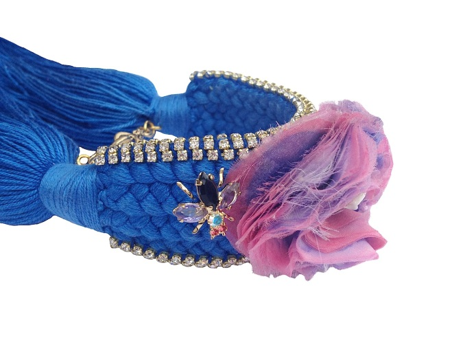 Colourful braided cuff handmade with a cobalt blue silk braid and embellished with small crystals, a handmade silk flower, dipped in gold bugs and a skull at the centre of the flower