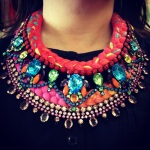 Two colourful statement necklaces layered together. Both pieces are made of bright braids. Prague in triple-dyed silk of fuchsia, salmon pink and a touch of yellow and St.Tropez statement necklace made with crystals and silk braid in vivid crimson mixing in a touch of neon green, blue, orange and yellow.