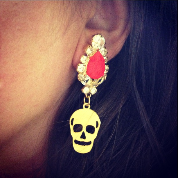 Glamorous statement earrings made with clear crystals, a dash of neon and embellished with brass skulls, dipped in gold.