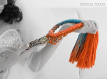 A model is holding Jolita Jewellery's colourful Brussels statement necklace made with a dip-dyed silk braid in turquoise and peachy orange with rhinestones hand-painted in soft pastels. This was a shoot for Crystal Touch boutique in Kuwait
