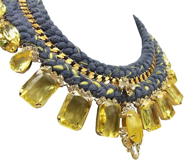 A luxury Portofino statement necklace, made with a double collar charcoal silk braid, mixing in a touch of citrine yellow. The collar is embellished with a gold-plated chain, intricately hand-stitched between the two silk braids. The necklace is adorned with an array of luxury deconstructed jewels, dipped in gold, including a little luxury bug in clear crystals.
