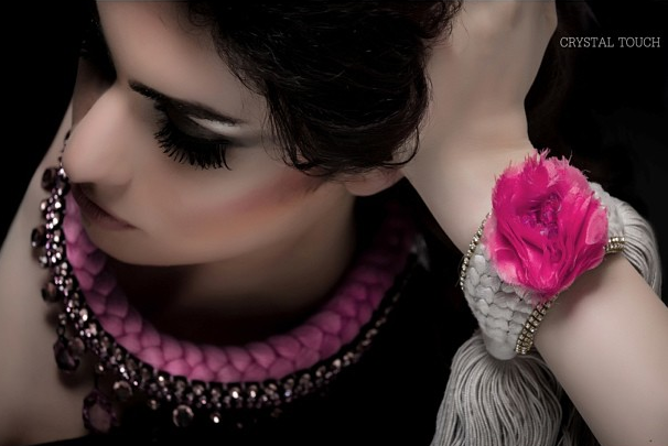 A model is wearing Jolita Jewellery's braided Prague statement necklace made with pink bohemian style rhinestones and dip-dyed silk braid in fuchsia and crimson and a braided cuff in grey silk and fuchsia silk rose, embellished with Swarovski crystals. This was a shoot for Crystal Touch boutique in Kuwait.
