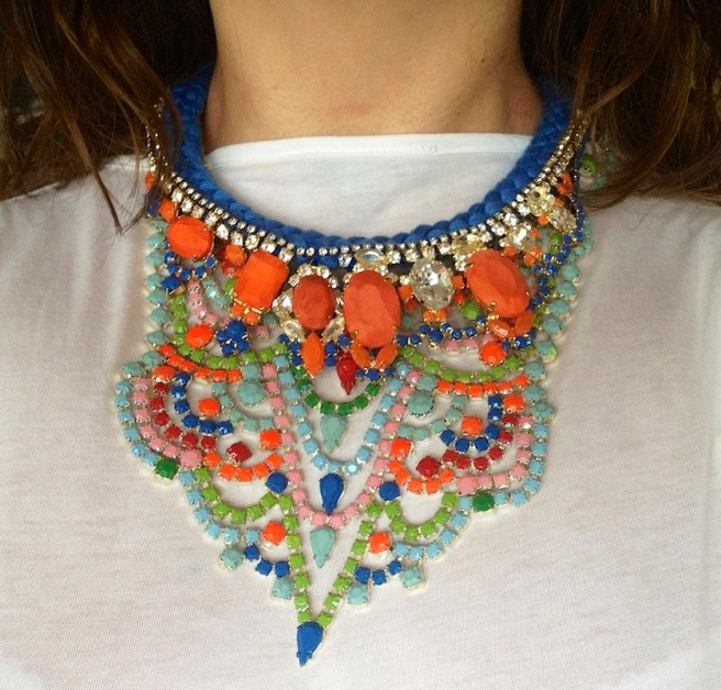 Two necklaces worn together: a hand-painted bib-style Carnival necklace and a luxury statement necklace Las Vegas, made with a blue silk braid and embellished with deconstructed jewels dipped in gold. Some crystals are hand-painted, some covered in hand-dyed silk.