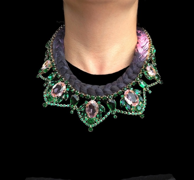 A bright colourful statement necklace made with dipped in gold crystals and dip-dyed silk braid in black with a splash of fuchsia pink