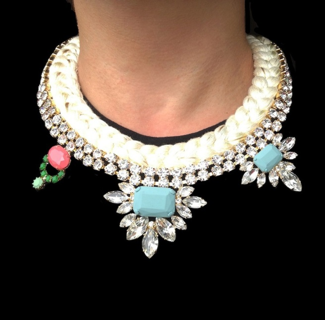 Hand-made statement necklace by Jolita Jewellery, made with a cream-white silk braid, mixing in a touch of champagne and embellished with clear asymmetric crystal necklace dipped in gold. Some of the crystals are hand-painted in soft pastels.
