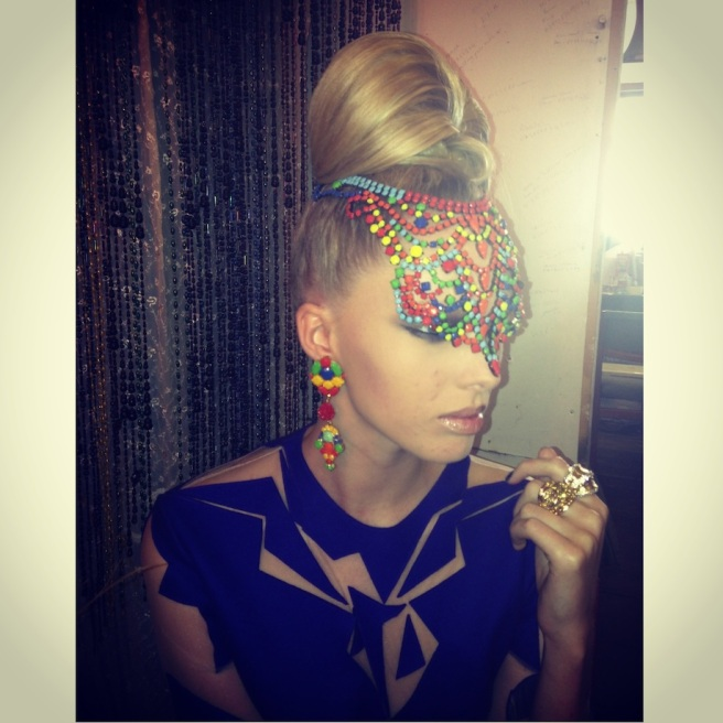 The model is wearing a colourful Salvador necklace by Jolita Jewellery and Havana earrings dipped in gold and hand-painted in an array of colours.
