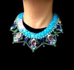 A bright colourful statement necklace made with dipped in gold crystals and dip-dyed silk braid in blue with a splash of fuchsia pink
