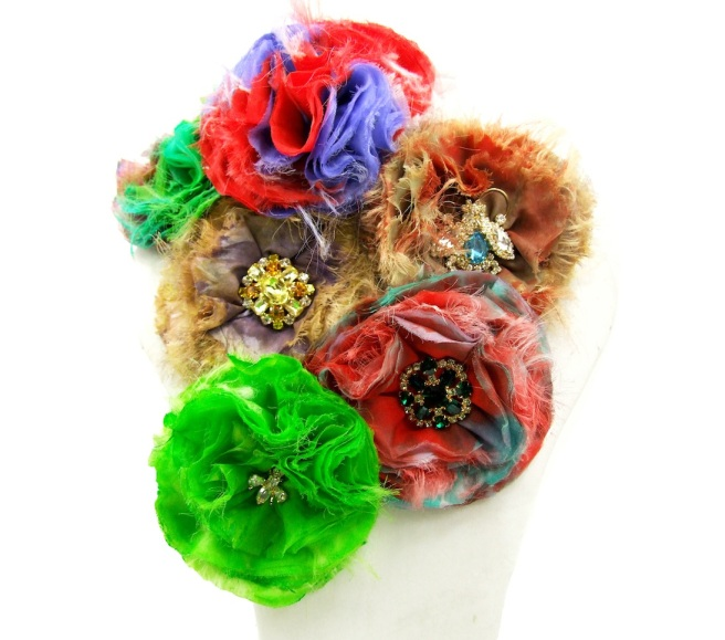 An array of colourful hand-made silk corsage made with silks dyed by Jolita Jewellery designer in his London studio and embellished with colourful rhinestones, dipped in gold.
