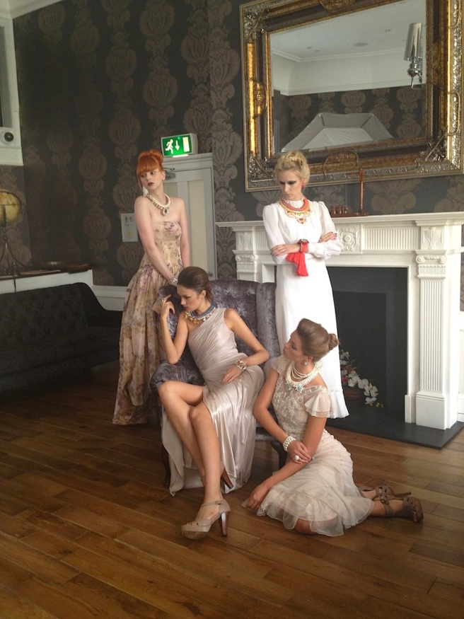 From recent fashion shoot - a group shot with four models posing in Jolita Jewellery pieces. Standing on the left - Sam in Casablanca necklace, Dasha in white dress and luxury Alexandria necklace, Beirut earrings and red braided cuff, sitting in the chair - Marina in luxury Antwerp necklace, asymmetric Naples necklace on Keeana, sitting on the floor.