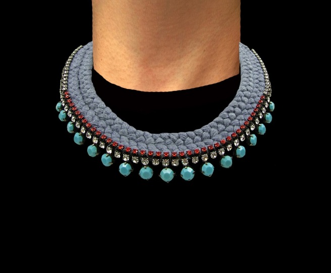 This statement collar is handmade by Jolita Jewellery. The necklace is embellished with three rows of turquoise, orange and clear crystals, and  braided with a double collar charcoal silk braid, hand-dyed by the designer in his London studio.