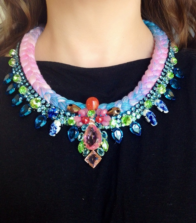 Santorini statement necklace designed by Jolita Jewellery with aquamarine and green  crystals and multicoloured dyed silk braid, gradually changing from pastel pink to sky blue, hand-dyed by the designer in his London studio. The necklace is adorned with crystal and semi-precious stones embellishment at the centre and porcelain skulls at the side.