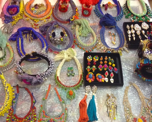 Colourful Jolita Jewellery statement necklaces, earrings and cuffs laid out for a fashion shoot