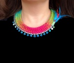 This bright statement necklace is created with a double collar hand-dyed silk braid in a multitude of tropical colours and aquamarine blue Swarovski crystals.The necklace is adorned with a small feather detail.