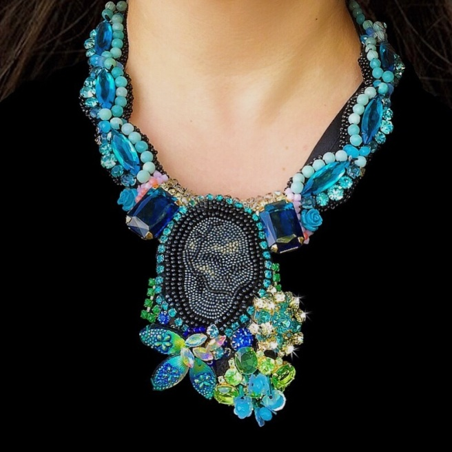 Unique Phantom statement necklace by Jolita Jewellery created with green and aquamarine blue crystals and a hand-beaded skull,  handmade using couture embroidery technique